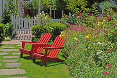 Red chairs. Two bright red chairs sitting by a colorful garden royalty free stock photo