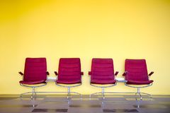 Red chairs against yellow wall. stock photo