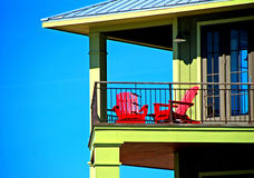 Red Chairs on Balcony. Bright red chairs on balcony of coastal home Royalty Free Stock Images