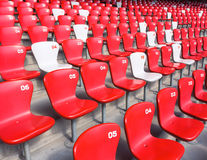 Red chairs bleachers in large stadium Stock Photo