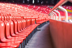 Red chairs bleachers in large stadium Stock Images