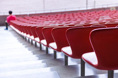 Red chairs bleachers in large stadium Royalty Free Stock Photos