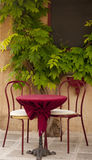 Red chairs and cafe table on terrace Stock Photos