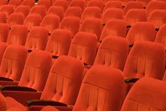 Red chairs in the opera house. Several rows of comfortable armchairs in the opera house. Shallow depth of field is used to place only few in focus stock photo