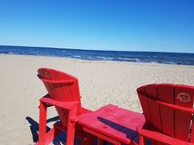 Red chairs in thé kouchibouguac national parc, new Brunswick, canada. Red chairs on a canadian beach stock photo