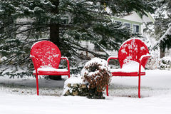 Red chairs in snow. Two bright red chairs set out in the snow.  Either too late or too early for the season. Location: Berkshires of Massachsetts Royalty Free Stock Photo