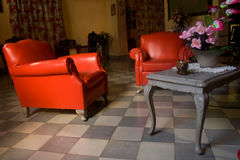 Red chairs and a table. Interior: red chairs and a table with flowers in vase royalty free stock image