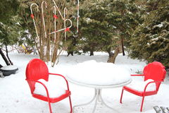 Red chairs and table in snow Stock Images