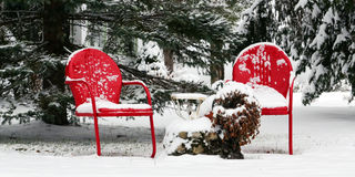 Red chairs, white snow. Two bright red chairs set out in the snow. Either too late or too early for the season. Location: Berkshires of Massachsetts royalty free stock image