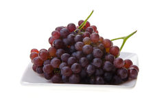 Red champagne grapes on white plate Royalty Free Stock Photo