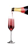 Red champagne pouring in a glass. Stock Photos