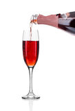 Red champagne pouring in a glass. Royalty Free Stock Images
