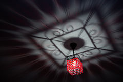 Red chandelier casting chic shadow on the ceiling Royalty Free Stock Photography