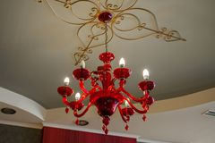 Red chandelier on a patterned ceiling in a dark room, glowing bulbs on it royalty free stock image