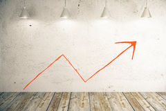 Red chart arrow on wall Stock Image