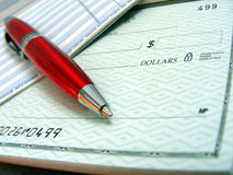 Red Check Bank Pen. A red pen is on top of a blank check Stock Photography
