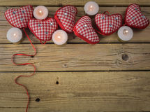 Red check hearts with candles on rustic wooden background Stock Image