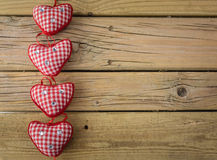 Red check hearts on rustic wooden background Stock Photos
