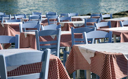 Red check tablecloths blue cha. A pattern of tables covered by red checked tablecloths whith blue painted wooden chairs sits alongside the  water of the harbor Royalty Free Stock Images