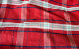 Red Checked Fabric Background. Closeup shot of red checked fabric with waves and folds Royalty Free Stock Image