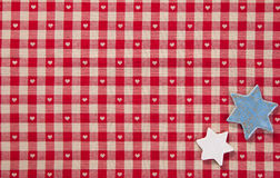 Red Checked Fabric And Stars. Background of two silver stars lying on colourful fresh red checked fabric with tiny hearts Stock Photography