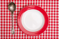 Red checked table cloth with plate and spoon Royalty Free Stock Photography