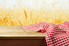 Red checked tablecloth on wooden deck table over wheat field background Stock Photography