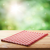Red checked tablecloth on wooden deck table. Summer background. Mockup for design Royalty Free Stock Photo