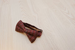 Red checkered bow tie on light wooden background Stock Image