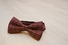 Red checkered bow tie on light wooden background Royalty Free Stock Photo