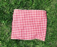 Red checkered cloth on green grass top view. Red checkered picnic cloth over green grass top view royalty free stock photography