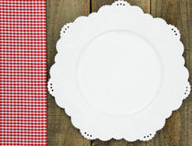 Red checkered fabric border next to white plate on rustic wooden table. Sign with red gingham (plaid) napkin next to white dish on rustic wood background Stock Photo