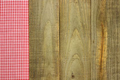 Red checkered fabric border on rustic wooden sign. Red gingham (plaid) fabric border on rustic wood table Royalty Free Stock Photos