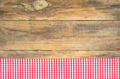 Red checkered fabric tablecloth on brown wooden table. Royalty Free Stock Photo
