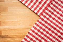 Red checkered fabric on wood table background.For decoration