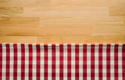 Red checkered fabric on wood table background.For decoration stock image