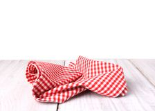 Red checkered gingham picnic cloth on table isolated. Red gingham checkered picnic cloth on wooden table isolated Royalty Free Stock Photo
