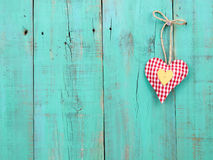 Red checkered and gold hearts handing on antique green wood door