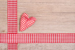 Red checkered heart and ribbon on wood Royalty Free Stock Photography