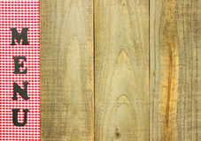 Red checkered MENU border on rustic wood sign. Red gingham (plaid) MENU border on weathered wooden table Royalty Free Stock Photos