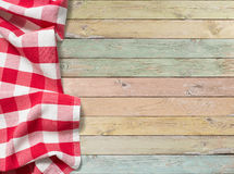 Red checkered picnic tablecloth on colorful wood table. Red checkered picnic tablecloth on colorful wooden table Royalty Free Stock Photo