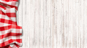 Red checkered picnic tablecloth on subtle wood table. Red checkered picnic tablecloth on subtle wooden table Royalty Free Stock Photos