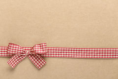 Red checkered ribbon bow on brown paper Royalty Free Stock Image