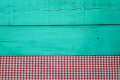 Red checkered tablecloth bodrer on antique green wooden background Stock Photo