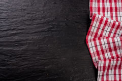 Red checkered tablecloth on a dark stone background with copy space for your text. Top view Royalty Free Stock Images
