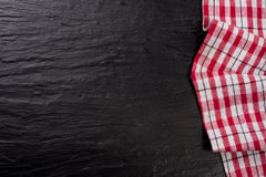 Red checkered tablecloth on a dark stone background with copy space for your text. Top view Stock Photography