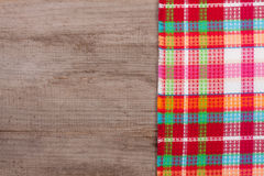 Red checkered tablecloth on an old wooden table with copy space for your text. Top view Royalty Free Stock Photos