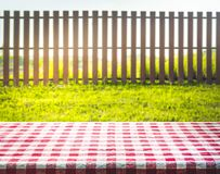 Red checkered tablecloth texture top with view garden, fence. Field background Royalty Free Stock Images