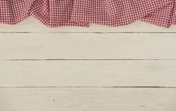 Red checkered tablecloth on white wood background. Red checkered table cloth on white wood background with space for a message Royalty Free Stock Photo