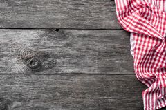 Red checkered textile on rustic wood. Food background. With copy space for text. Picnic, menu, restaurant, home cooking concept Stock Photos